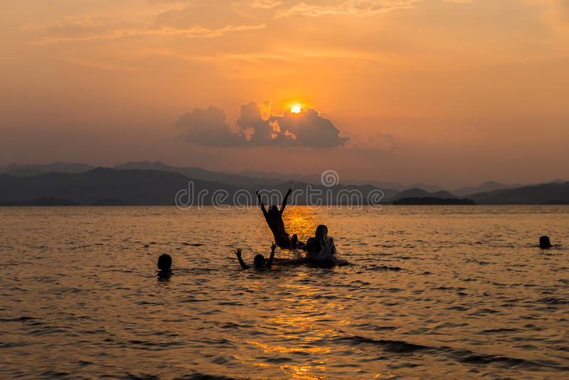 Silhouette Of Multi Generation Family Having Fun In lake. At sunset stock image