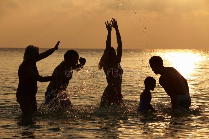 Silhouette Of Multi Generation Family Having Fun In Sea. Playing stock photo