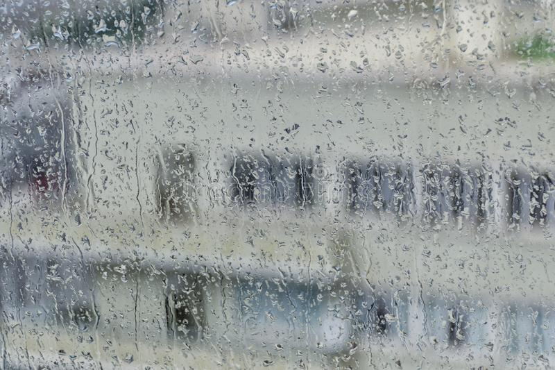 Silhouette of a multistory building with white walls and windows on the background of a wet glass with rain streaks. Silhouette of a high rise building with stock image