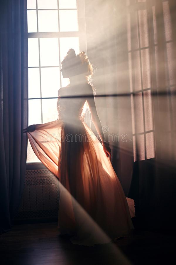 Silhouette of a mysterious fairy woman on the background of the window in the sunlight. Girl in the sunlight of the early morning royalty free stock image