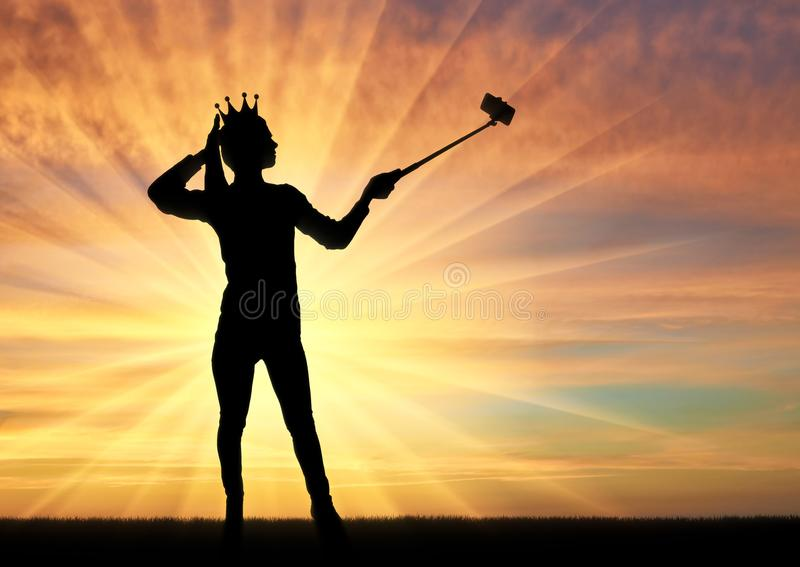 A silhouette of a narcissistic and selfish woman with a crown on her head, makes selfie on the phone stock photo