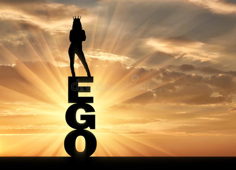 Silhouette of a narcissistic and selfish woman with a crown on her head standing on the word ego stock photography
