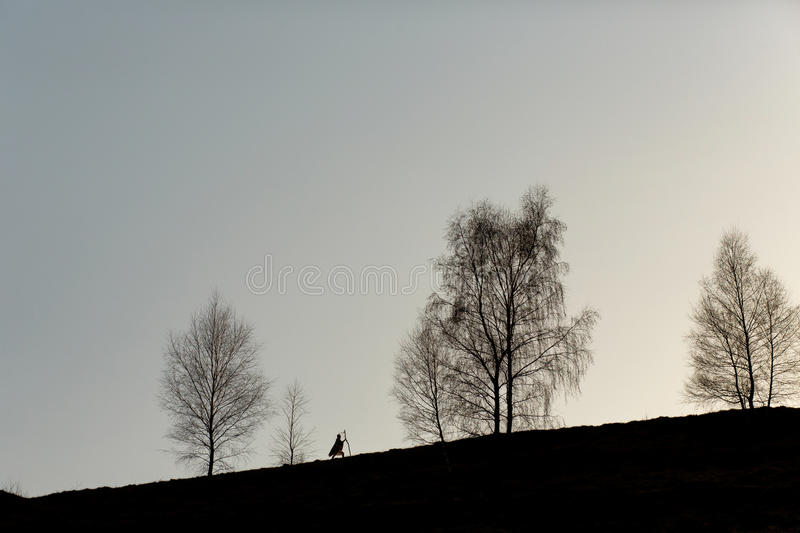 Silhouette of native indian american woman walking on hill among. Trees in sunset evening mountains royalty free stock photos
