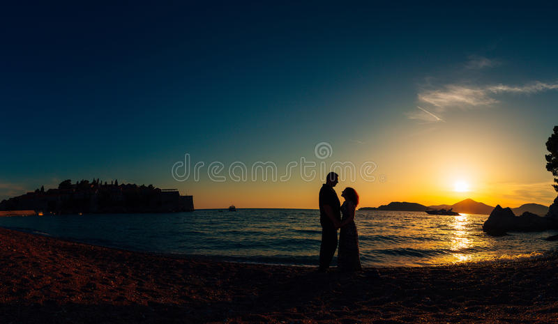 Silhouette of a newlywed couple at the sea at sunset. Wedding in. Montenegro. Silhouettes of the couple, the bride and groom royalty free stock photography
