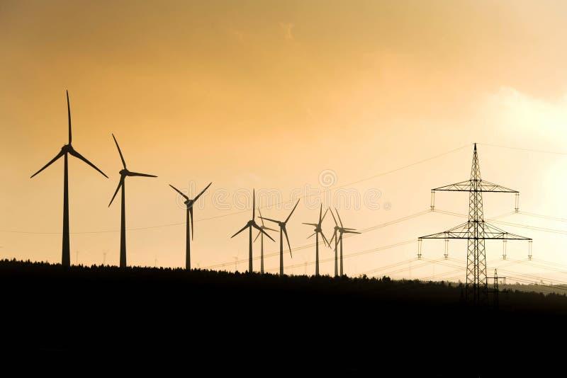 Silhouette noire de générateur d'énergie de windturbines sur le coucher du soleil étonnant à une ferme de vent en Allemagne image libre de droits