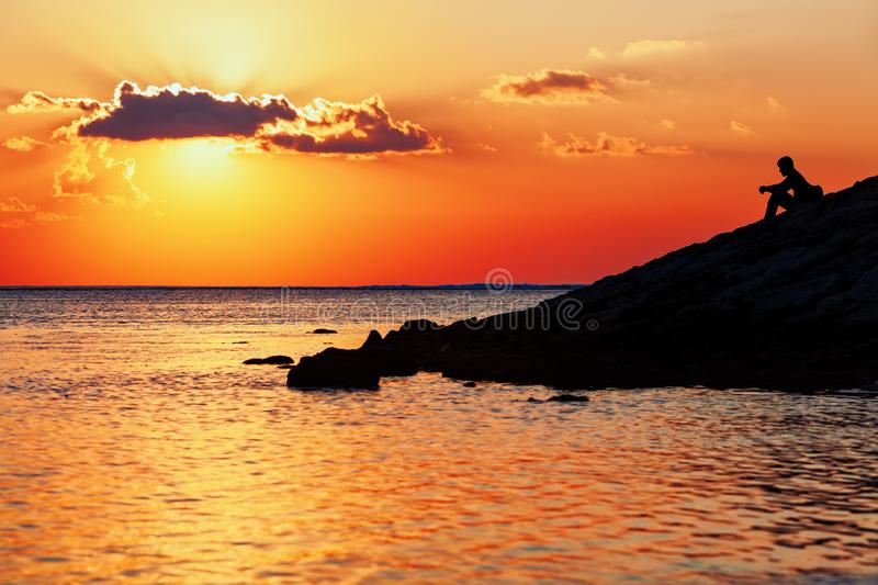 Silhouette noire de jeune homme se reposant sur la plage de mer de coucher du soleil photographie stock