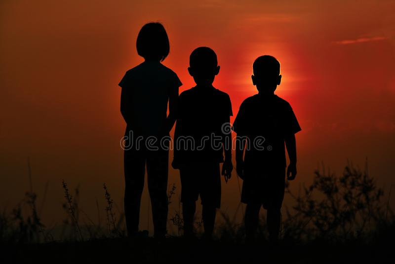Silhouette noire de trois enfants se tenant ensemble Il y a un ciel au coucher du soleil photographie stock libre de droits