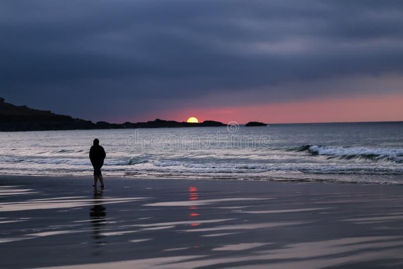 Silhouette noire et blanche de l'homme seul marchant sur la plage pendant le Su image stock
