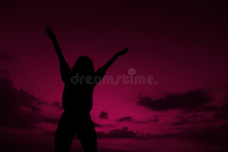 Silhouette noire femelle avec les mains augmentées sur le fond violet de ciel de coucher du soleil dans Bali photographie stock libre de droits