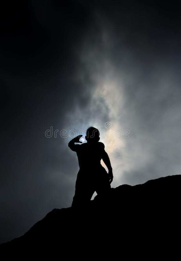 Free Silhouette Of Man Standing On Rock Reaching Up To The Sky During Partial Eclipse Stock Photo - 133687440