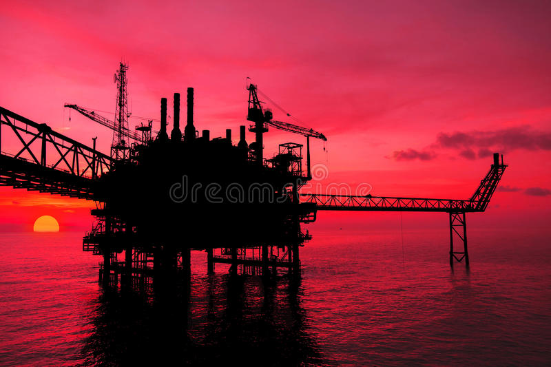Silhouette,Offshore oil and rig platform. In sunset or sunrise time. Construction of production process in the sea. Power energy of the world royalty free stock image