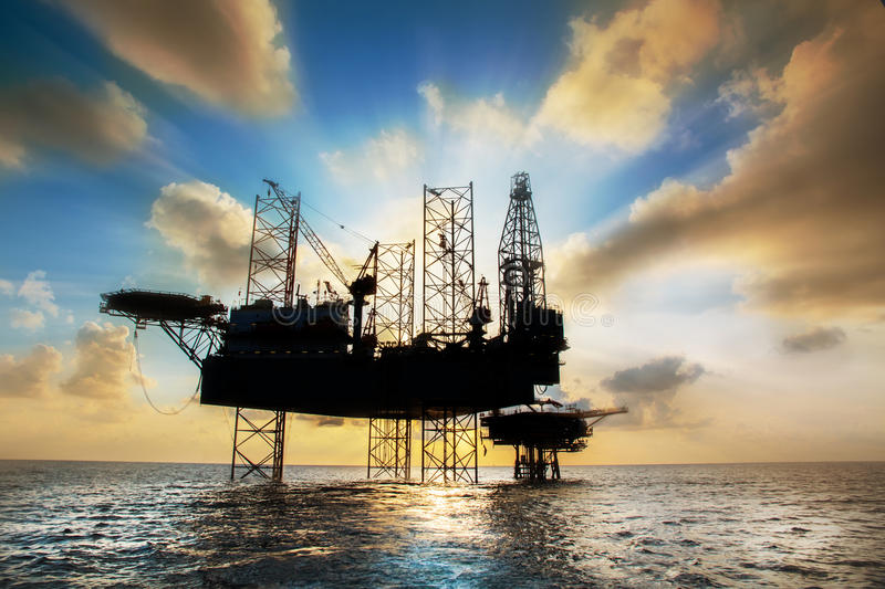 Silhouette,Offshore oil and rig platform. In sunset or sunrise time. Construction of production process in the sea. Power energy of the world royalty free stock photography