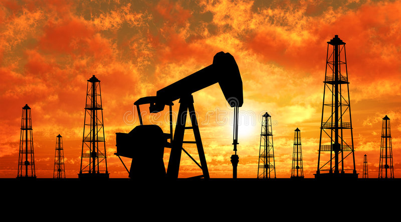 Silhouette oil rigs and pumps stock photography