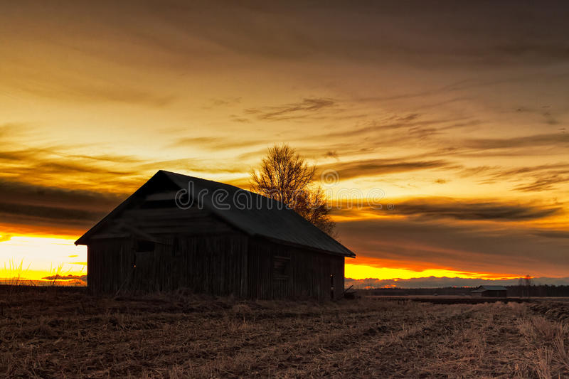 Silhouette Of An Old Barn House. A lonely old barn house stands on the springtime fields of the Northern Finland. The sun sets beautifully behind it royalty free stock photography