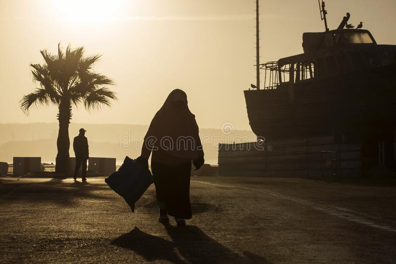 Silhouette of an old woman carrying a back on the seashore of the ocean, passing next to an old boat with pigeon resting on it royalty free stock photos
