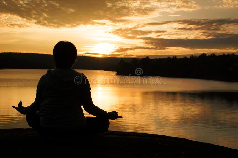 Silhouette of old woman yoga near lake during sunset royalty free stock photo