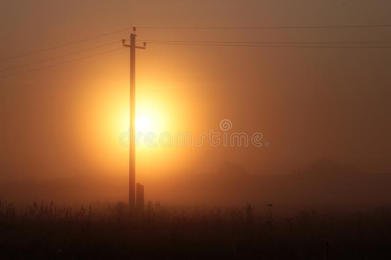 Silhouette of an old wood electrical tower at sunset. Summer background stock photos