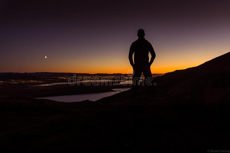 Silhouette Overlooking a city at sunset. Silhouette looking down at Reykjavik at sunset. The moon can be seen hovering over the horizon, giving a cool focus royalty free stock image