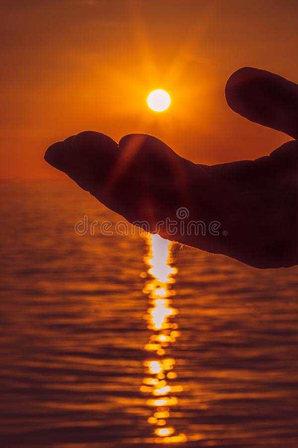 Silhouette of a palm of a hand almost touching the setting sun over an ocean. The rays of the sun can be seen. royalty free stock image
