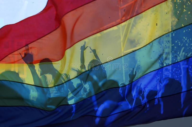 silhouette of a parade of gays and lesbians with a rainbow flag - symbol of love and tolerance royalty free stock images