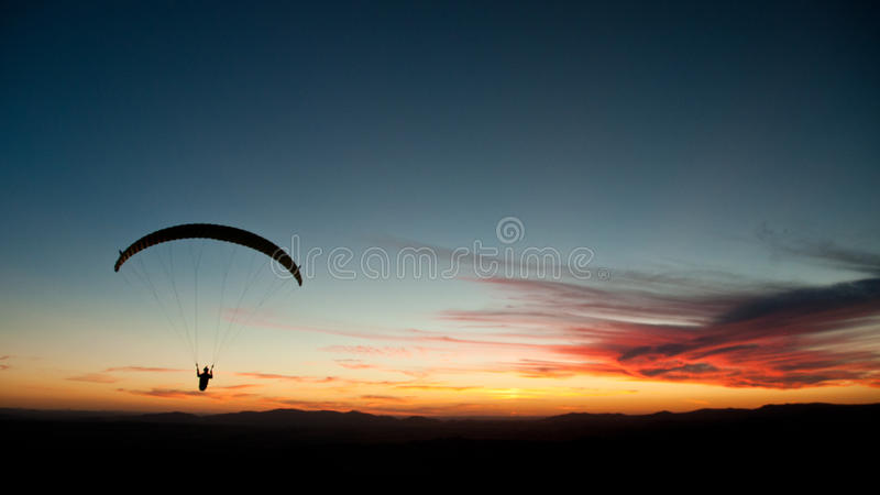 Silhouette of paraglider at sunset. stock photos
