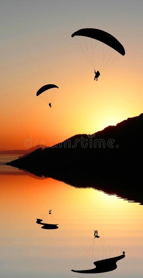 Silhouette paragliders in coastal sunset landscape. Two silhouette paragliders flying in the sunset sky, coastal landscape with water reflection, romantic mood royalty free stock images