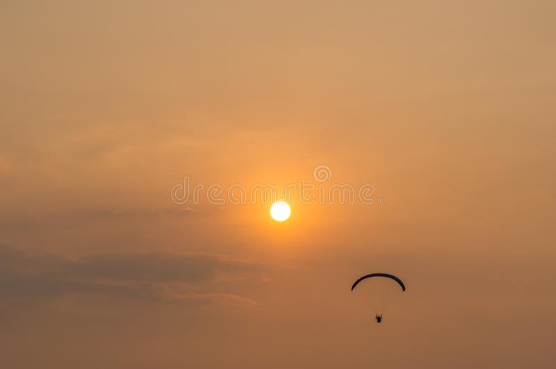 Silhouette of paramotor with sunset sky.  stock image