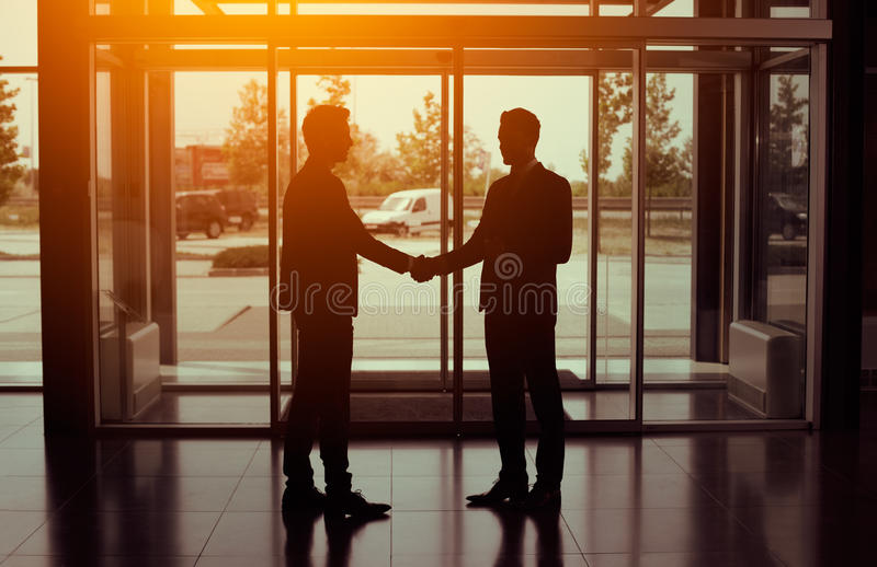 Silhouette of partnership handshake stock image