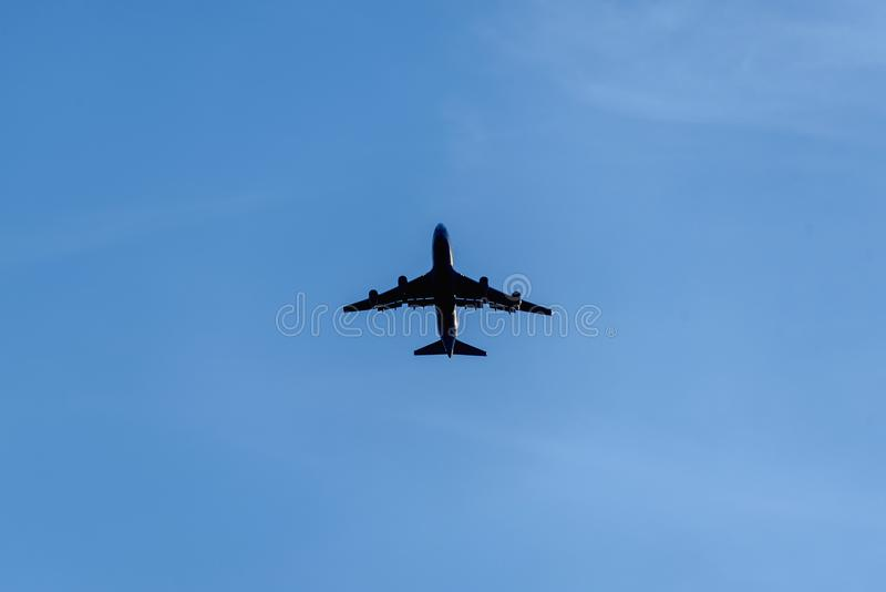 Silhouette of a passenger airplane on a background of an empty blue sky. Aviation, passenger transportation, travel, flight stock photos