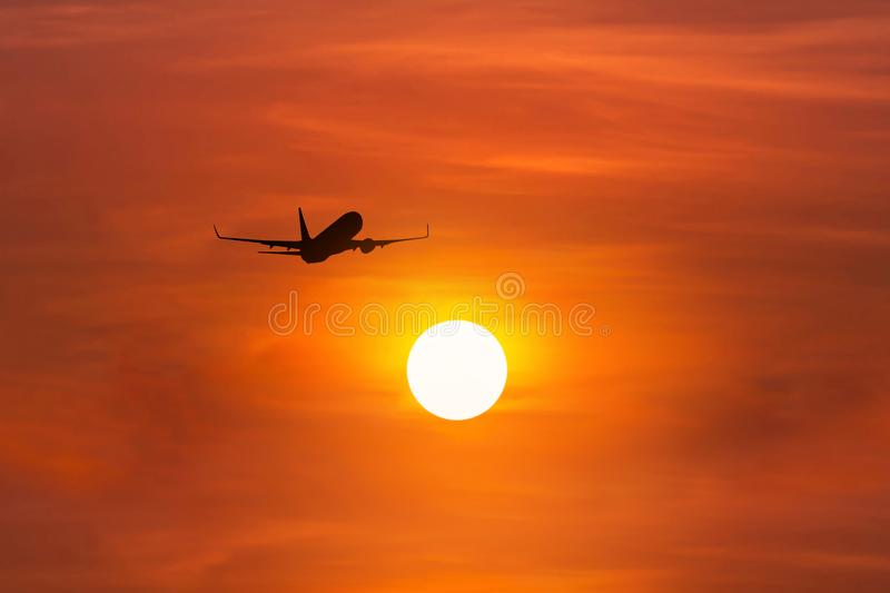 Silhouette passenger airplane flying away in to sky high altitude above the sun during sunset time. Travel destinations concept stock image