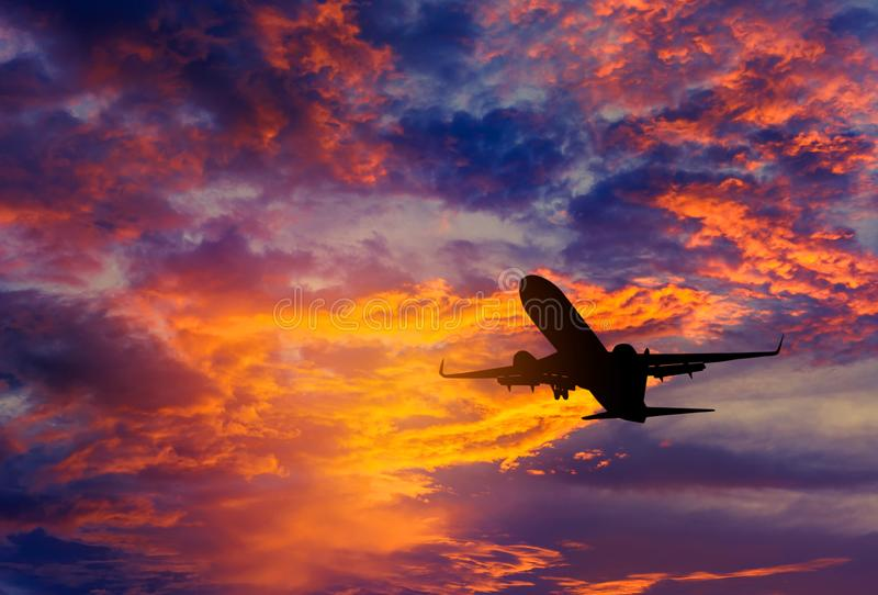 Silhouette passenger airplane flying away in to sky high altitude during sunset time. Travel destinations concept stock image