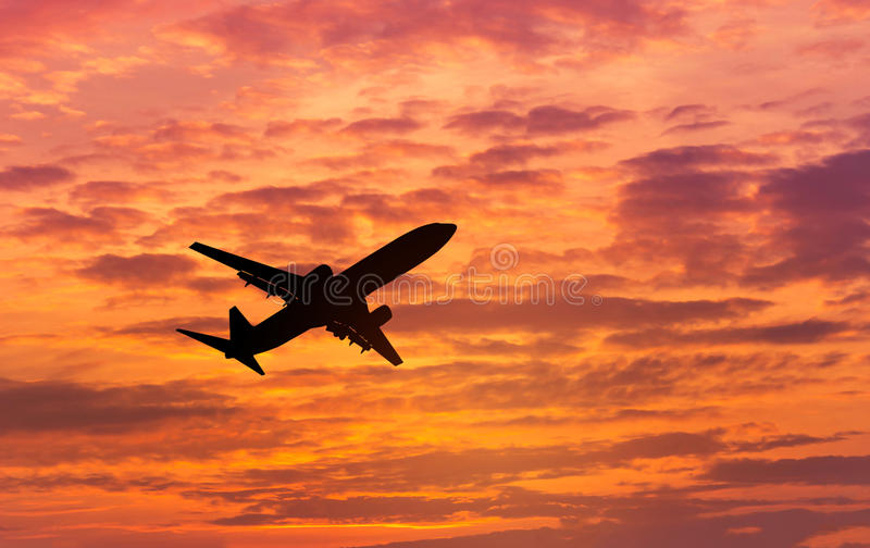 Silhouette passenger airplane flying on sunset royalty free stock image