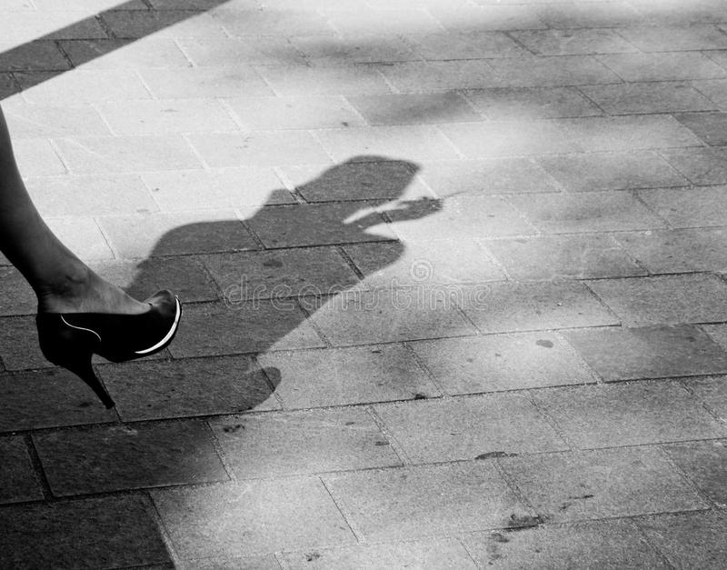 Silhouette on a pavement. Silhouette of a woman smoking on a pavement stock image