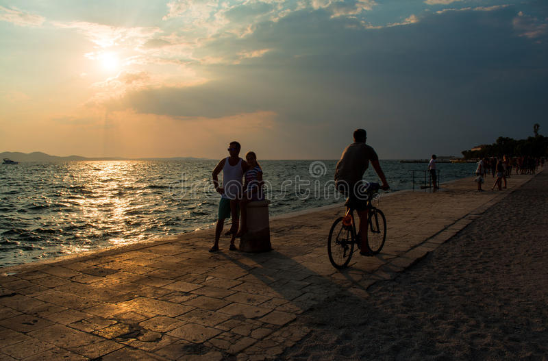 Silhouette of people on the beach. At sunset royalty free stock photography