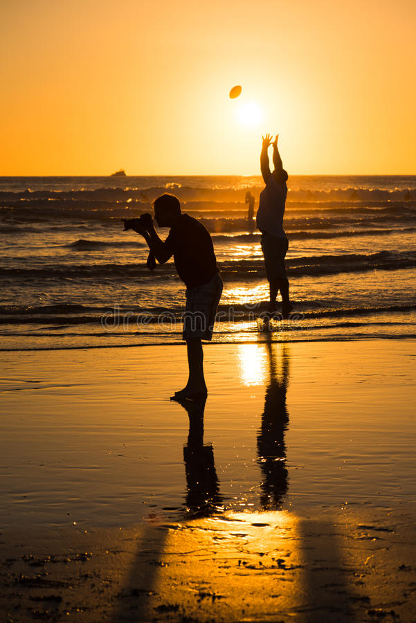 Silhouette of people at the beach. At sunset stock images