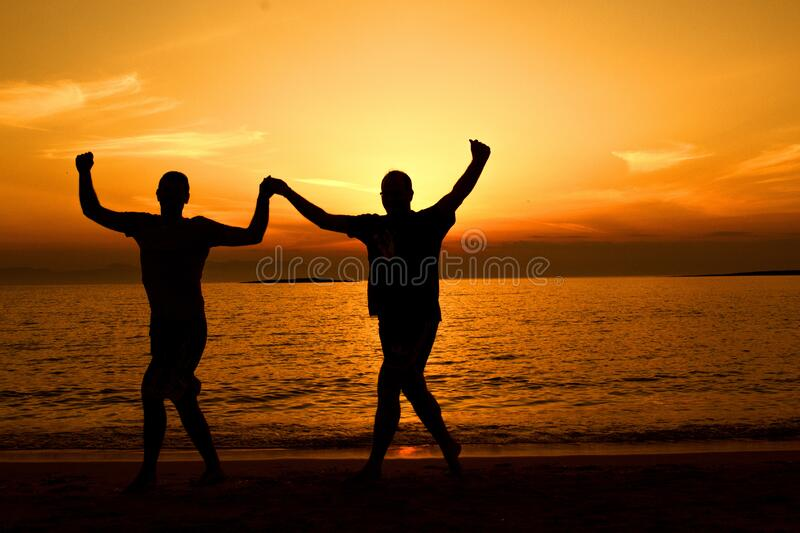 Silhouette People on Beach at Sunset royalty free stock photo