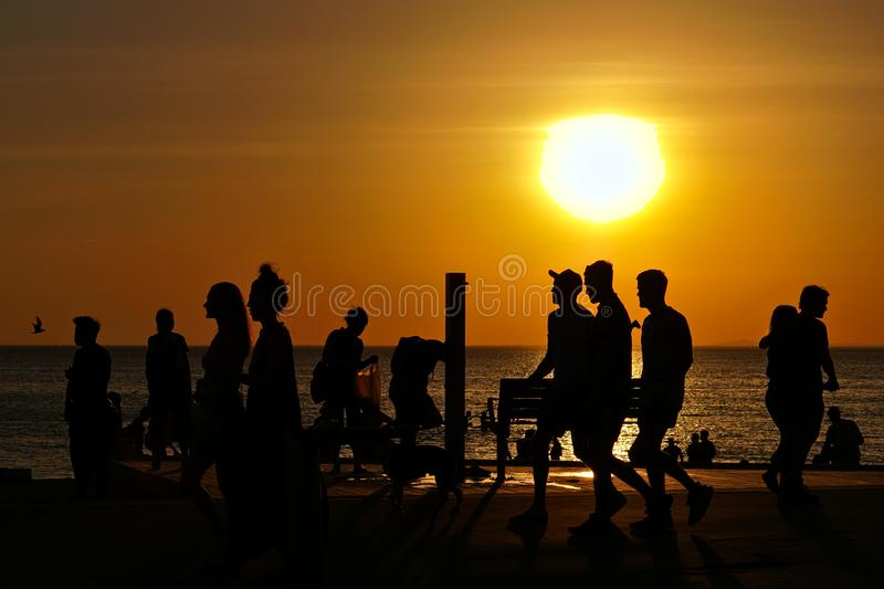 Silhouette of people and beach during sunset. St Kilda, VIC / Australia - Oct 31 2019: View of silhouette of people and beach during sunset royalty free stock images
