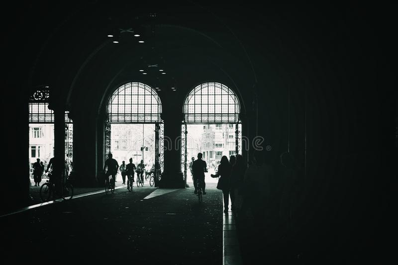 Silhouette of people and bicycles in a tunnel stock image