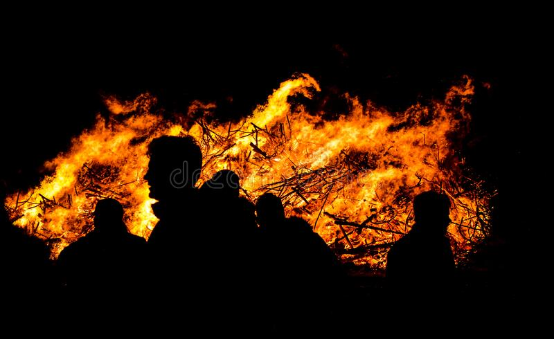 Silhouette of people by bonfire stock image