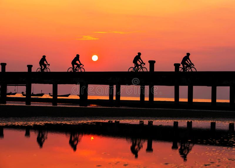 Silhouette People are cycling in the evening. stock photo