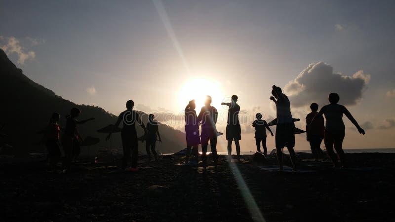 Silhouette of people doing Yoga at sea coast sunrise time. Adrasan Beach Turkey Yoga at sunrise stock images