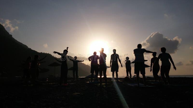 Silhouette of people doing Yoga at sea coast sunrise time. Adrasan Beach Turkey Yoga at the beach stock photos