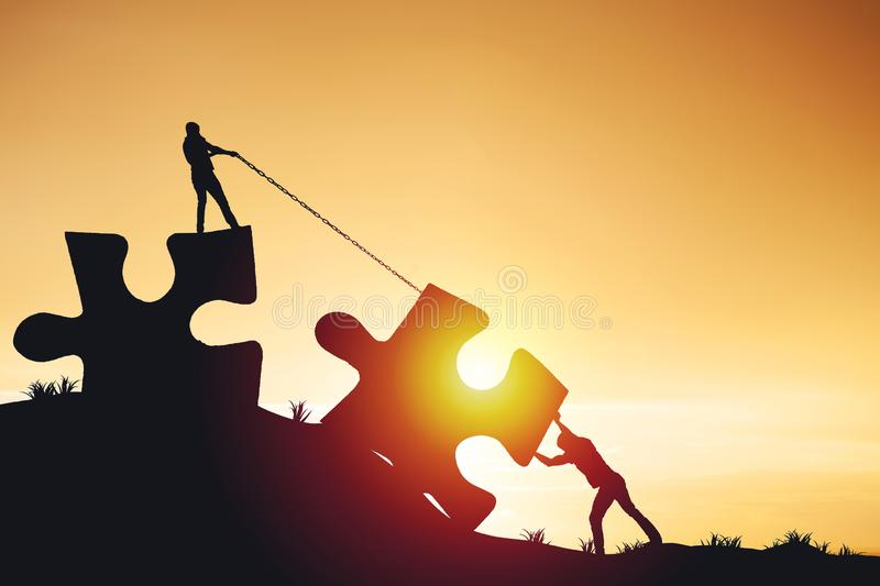 Silhouette people helping to connect jigsaw and puzzle to success stock photo