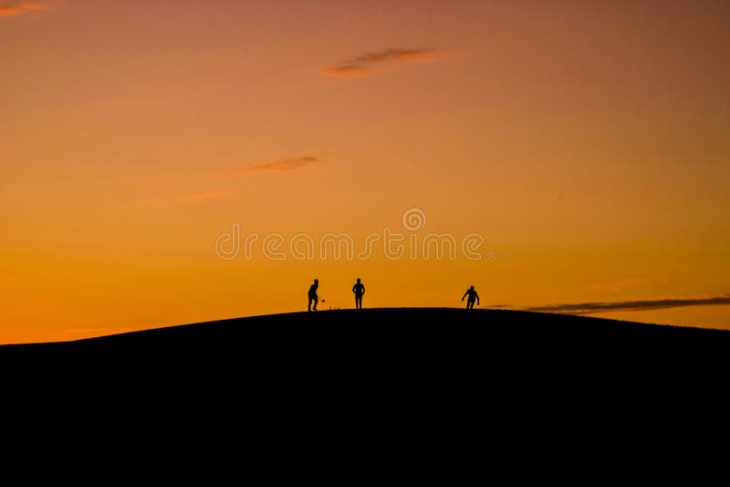 Silhouette of 3 People in Hill during Sunset royalty free stock images