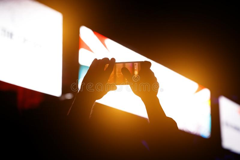 Silhouette of people holding their smart phones and photographing concert.  stock photography