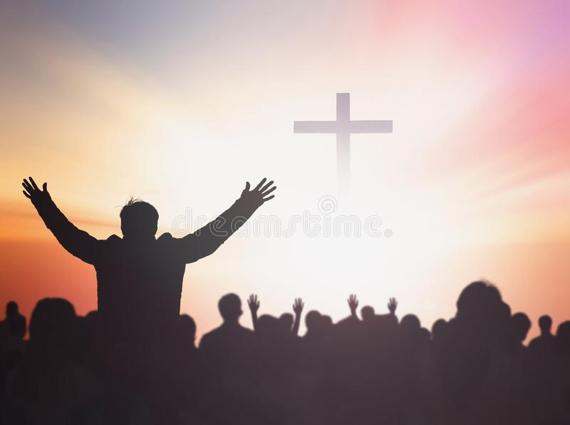 Silhouette people raising hands over blurred the cross on beautiful golden autumn sky sunset background royalty free stock photos