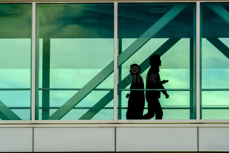 Silhouette of people seen through glass windows. Silhouette of two people walking inside a building seen through the transpaarent glass windows. Exterior of a stock images