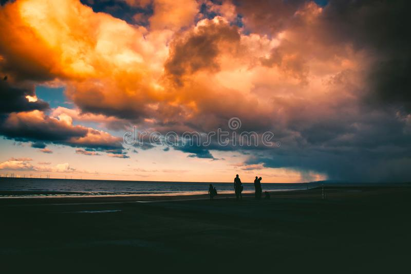 Silhouette Of People On Shore Under Cloudy Sky stock photos