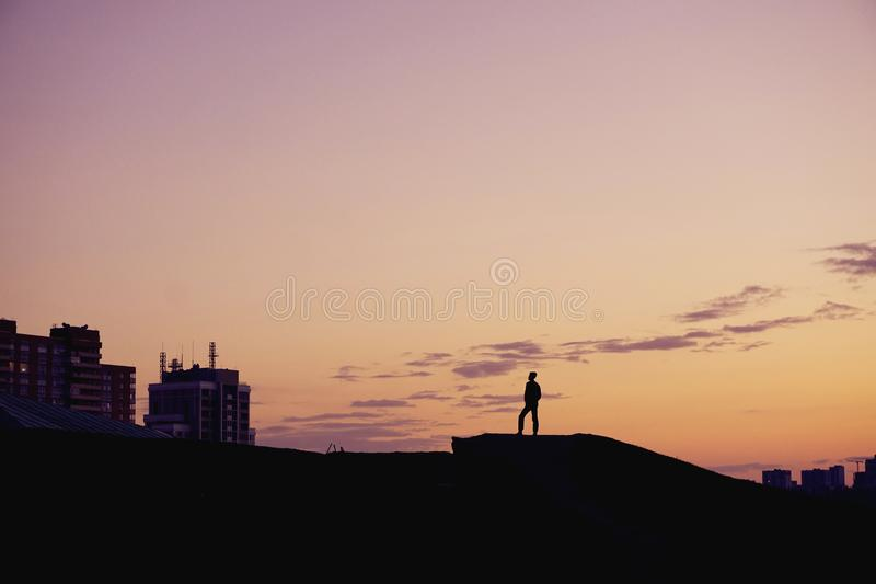 Silhouette people standing on hill at sunset time over city. stock image