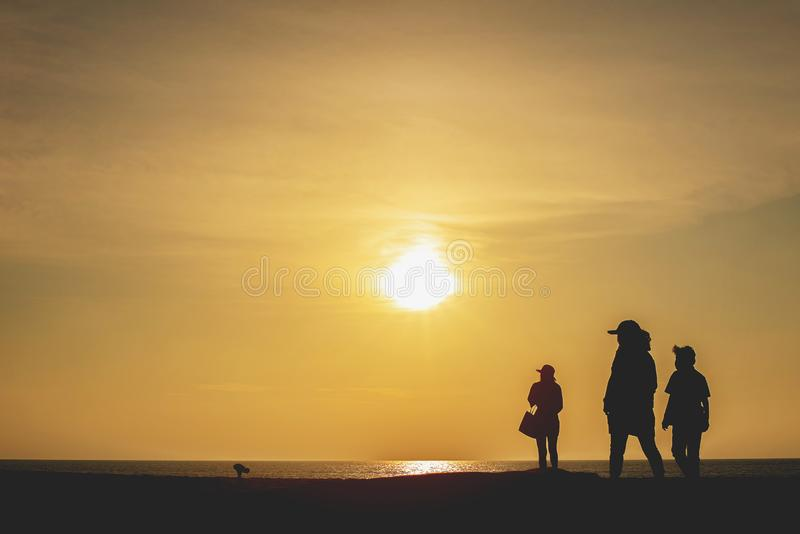 Silhouette of people standing and walking on the beach with sunset background stock photography